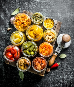 Preserved food on wooden tray. on dark rustic table