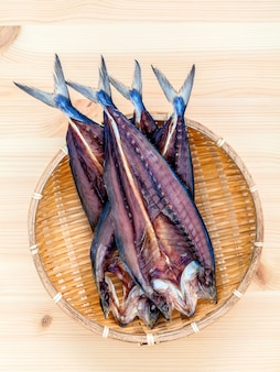 Preserved salted fish on wooden cutting board.