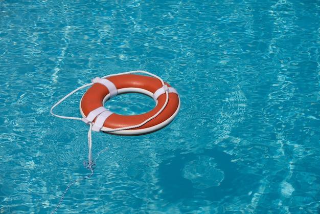 Спасательный круг оранжевый спасательный круг в море на воде спасательное кольцо, плавающее в воде