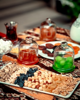 Сохраняет сухофрукты и орехи с фисташками на столе
