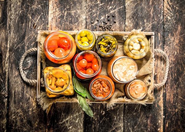 Консервы с овощами и грибами на старом подносе. на деревянном столе.