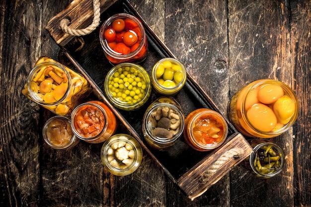 Консервы из грибов и овощей в ящике. на деревянном столе.