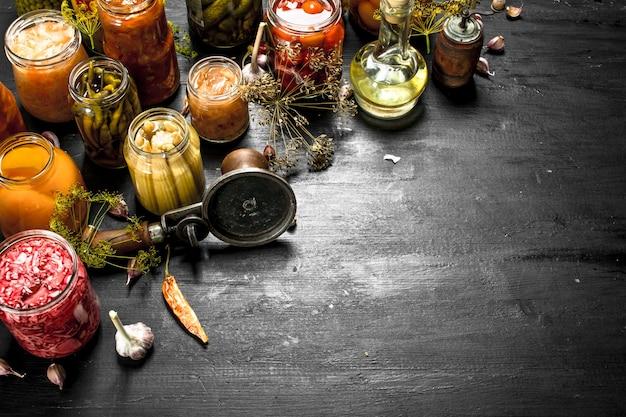 Консервы из грибов и овощей с закаточной машиной. на черной доске.