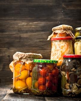 Консервы из овощей и грибов в стеклянных банках. на деревянном столе.