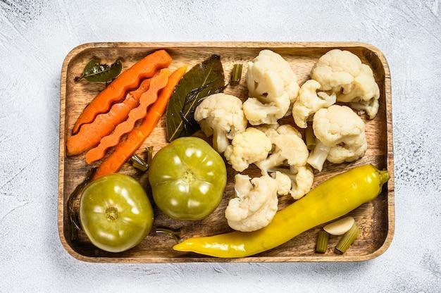 野菜、自家製のおいしい漬物を木製のトレイに保存します。白色の背景。上面図。