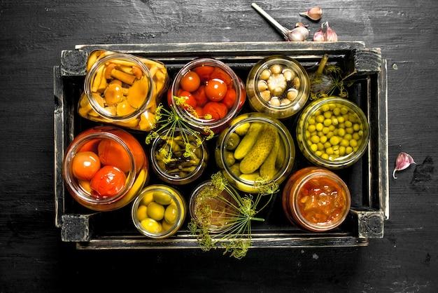Консервы овощи в стеклянных банках в старой коробке на черной доске.