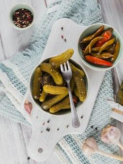 Консервирование маринованных огурцов, перца, приправ и чеснока на белом деревянном столе