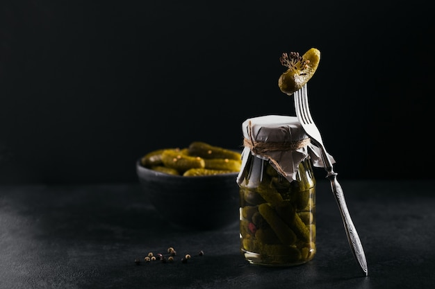 きゅうりのピクルス、調味料、にんにくを暗いテーブルに保存します。健康的な発酵食品。家庭用缶詰野菜。