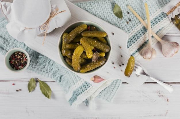きゅうりのピクルス、調味料、にんにくを白い木製のテーブルに保存。健康的な発酵食品。家庭用缶詰野菜。
