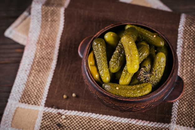 Консервирование маринованных огурцов, приправ и чеснока на деревянном столе. здоровая ферментированная пища. овощные консервы домашние.