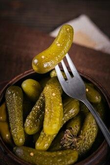 Консервирование маринованных огурцов, приправ и чеснока на деревянном столе. здоровая ферментированная еда