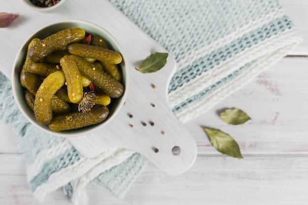 きゅうりのピクルス調味料とにんにくを白い木製のテーブルに保存