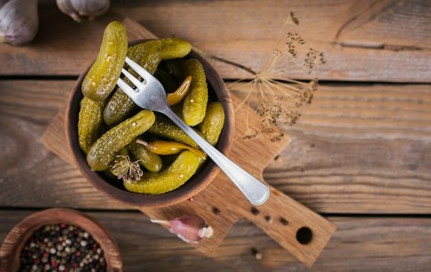 きゅうりのピクルス調味料とにんにくを木製のテーブルに保存