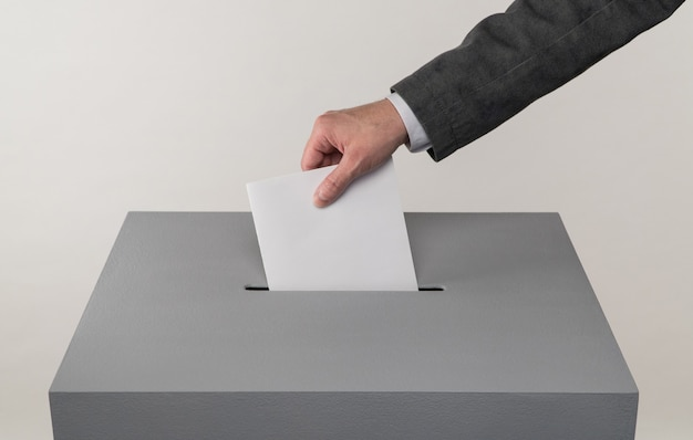 대통령 및 국회의원 선거 유권자가 투표용지를 투표함에 던집니다.
