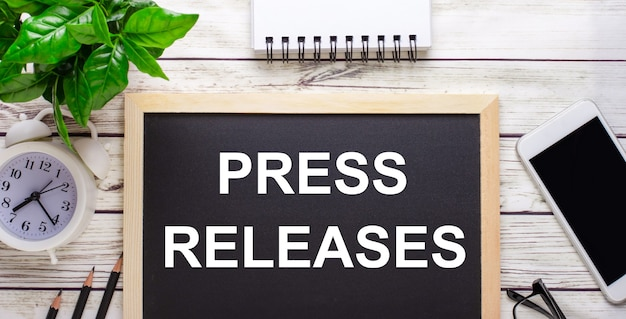Press releases written on a black surface near pencils, a smartphone, a white notepad and a green plant in a pot