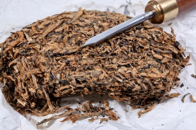 飲酒式用のプレスプーアル茶ケーキとナイフ。伝統的な中国の飲み物と中国からの人気の抗酸化飲料。