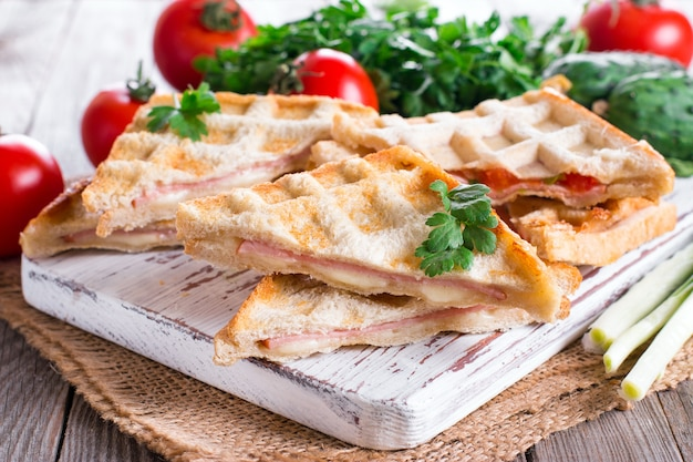 Pressed and toasted double panini with ham and cheese served on a wooden table