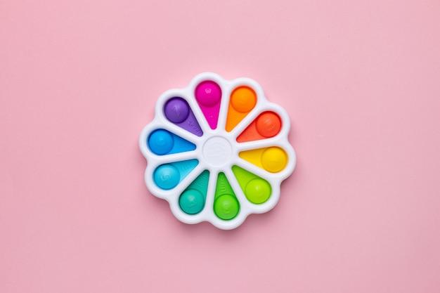 Нажимает пальцем игрушку-антистресс pop it на розовом фоне разноцветная силиконовая игрушка poppit bubble f ...