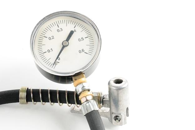 孤立した白の自動車タイヤのクローズアップの空気圧を測定するための圧力計 Premium写真
