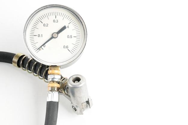 孤立した白の自動車タイヤのクローズアップの空気圧を測定するための圧力計