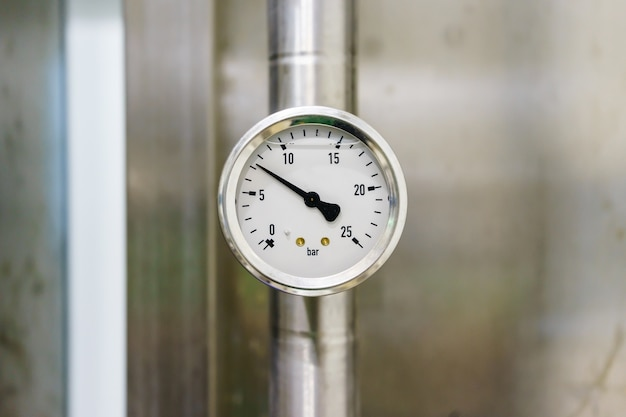 Pressure gauge in the pipeline, measuring instrument close up on pneumatic control system.