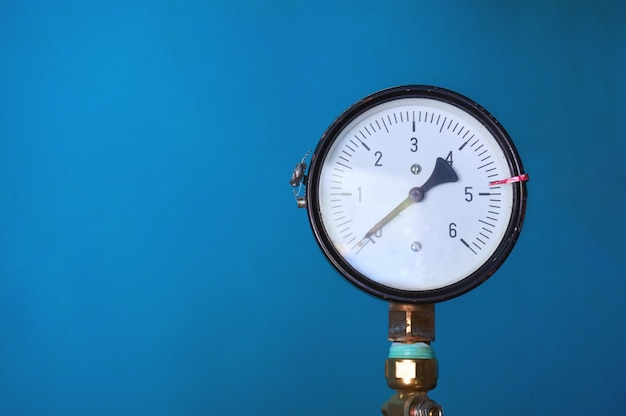 The pressure gauge shows zero pressure on a blue wall. abstract wall.