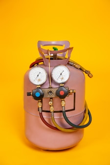 Манометры измерительные приборы для заправки кондиционеров, датчики. цилиндр с фреоном на желтом фоне. инструменты для hvac