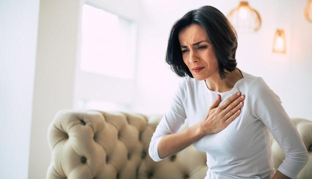 胸の圧力。胸の痛みに苦しんでいて、彼女の心臓領域に触れているストレスのたまった女性のクローズアップ写真。