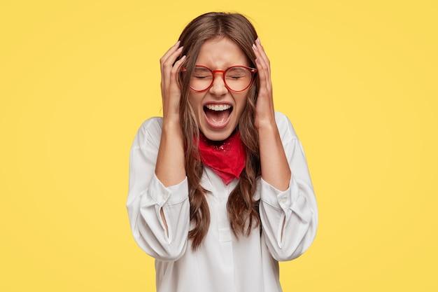 Давящая и усталая женщина держит руки за голову, у нее болит голова или мигрень, широко раскрывает рот и что-то восклицает