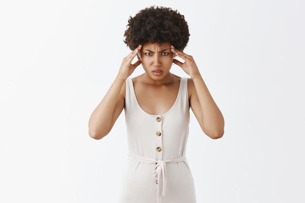 Ragazza alla moda sotto pressione in posa contro il muro bianco