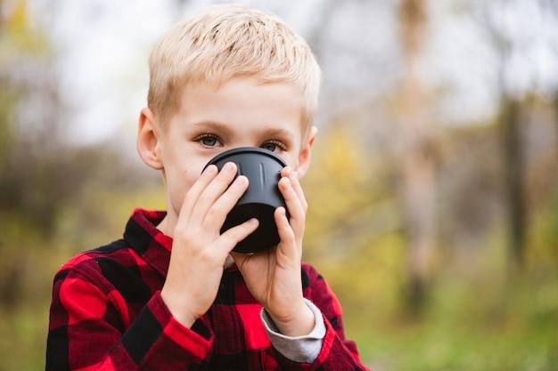 Двадцатилетний белокурый ребенок мужского пола в красной рубашке пьет горячий напиток из черной чашки термоса. счастливые семейные выходные в осеннем парке