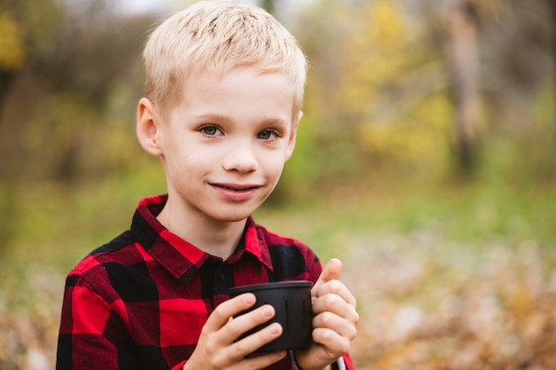 Двадцатилетний белокурый ребенок мужского пола в красной рубашке держит черный термос с горячим напитком. счастливые семейные выходные в осеннем парке.