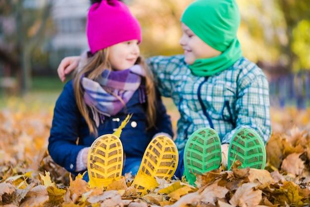 屋外で明るい雨靴のプレティーンの男の子と女の子