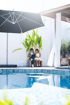 캐주얼 옷을 입은 십대 소년과 소녀는 낮에 수영장이 있는 고급 빌라에서 태블릿을 사용합니다.