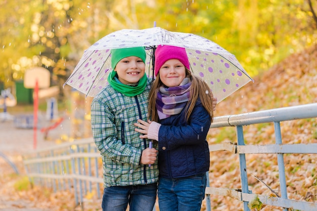 雨の公園を歩くプレティーンの男の子と女の子