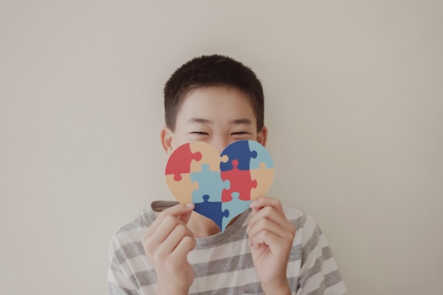 Preteen boy holding puzzle jigsaw, child mental health, world autism awareness day
