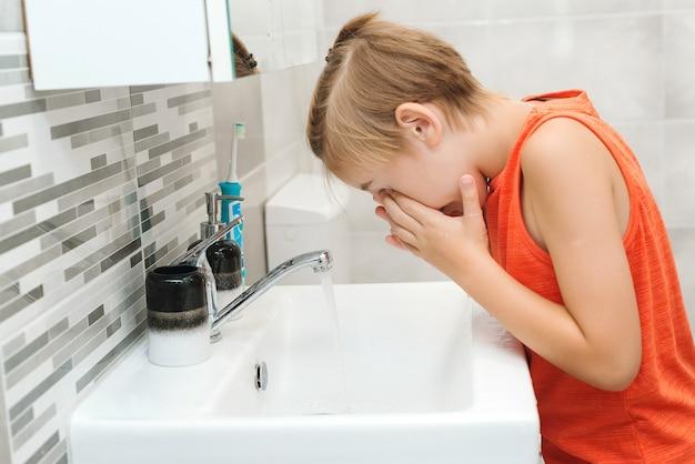 プレティーンの少年は洗面台で洗われます。健康的な子供時代とライフスタイル。男の子がトイレで顔を洗う。朝の衛生。毎日の歯科衛生。ヘルスケア、小児期および歯科衛生。