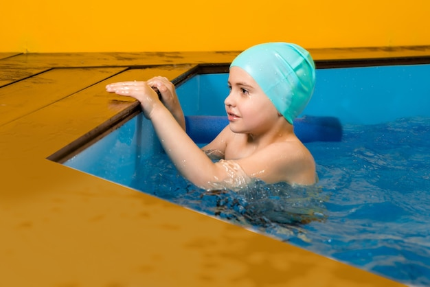Подросток мальчик плавает в крытом бассейне, развлекаясь во время урока плавания