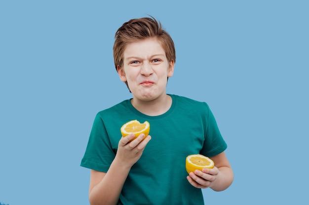 Малолетний мальчик пробует свежий лимон, кислый вкус, делает гримасу,