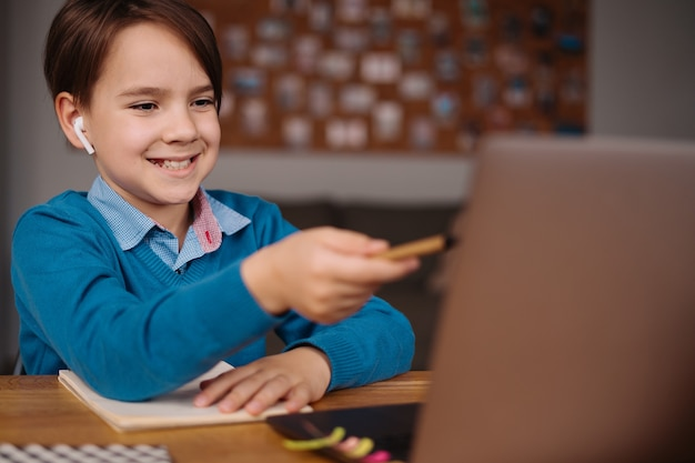 A preteen boy uses a laptop to make online classes