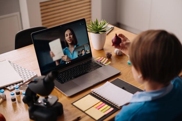 Un ragazzo preteen usa un laptop per fare una videochiamata con il suo insegnante