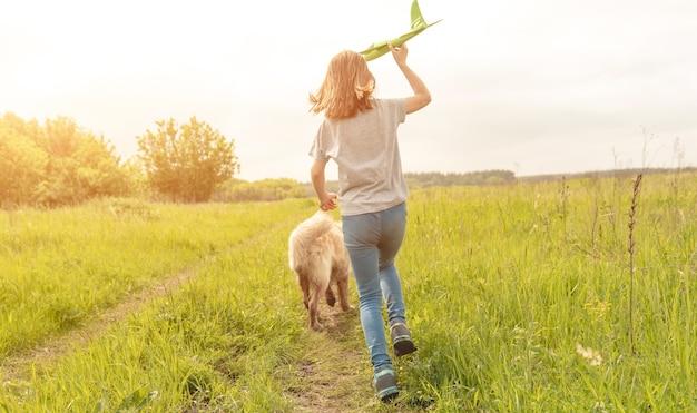 フィールドでゴールデンレトリバー犬と一緒に走っておもちゃの飛行機を持っているプレティーンの子供の女の子
