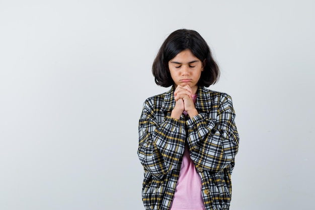 Preteen girl combining hands while wishing in shirt,jacket and looking focused , front view.