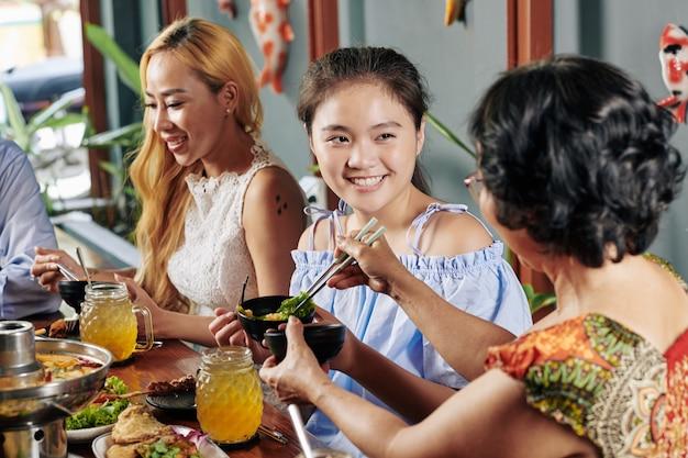 家族との夕食を楽しんでいるプレティーンの女の子