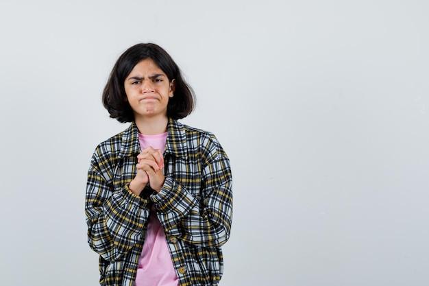 シャツ、ジャケット、焦りを合わせて手を合わせて立っている間、ニュースを期待しているプレティーンの女の子。正面図。テキスト用のスペース