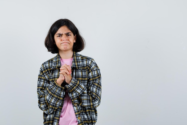 Preteen girl expecting news while standing with combined hands in shirt,jacket and looking impatient. front view. space for text