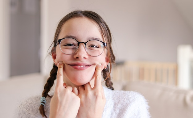Preteen girl in glasses with pigtails making artificial smile, april fools day