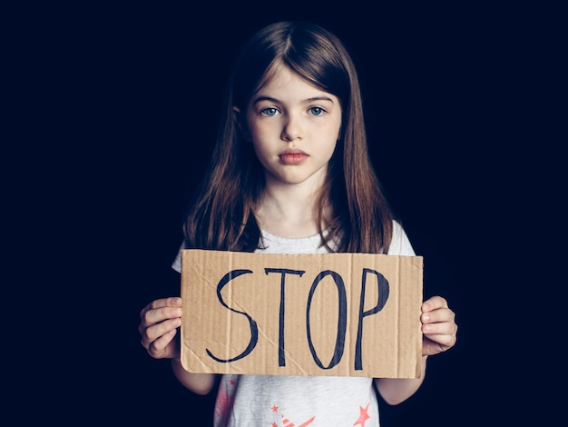 Preteen girl holding a sign stop, concept of problems, negative emotions, addiction of children and adolescents