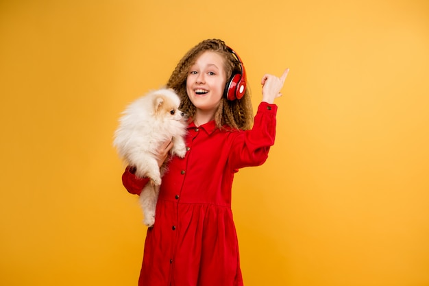 Preteen girl holding a small dog in her hands