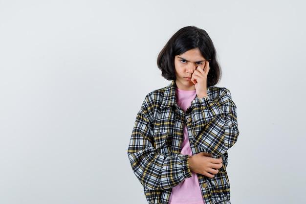 Девочка десятилетнего возраста в рубашке, куртке, держащей руку на щеке и недовольной, вид спереди. место для текста